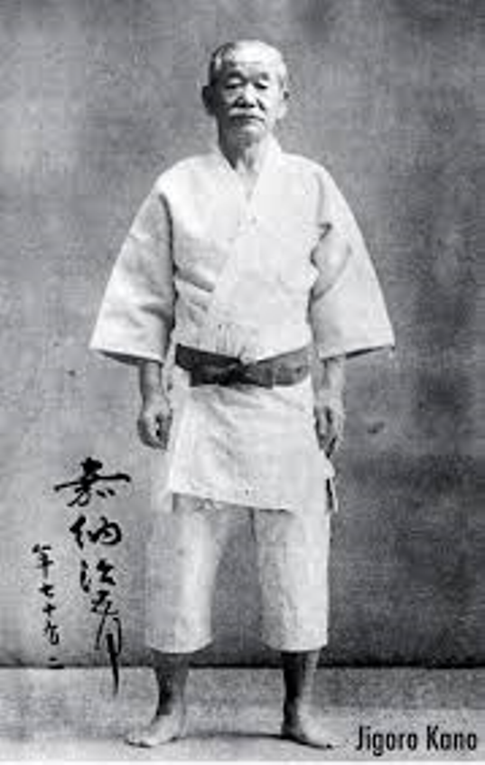 "Jigoro Kano the mastermind behind the Jiu-jitsu modernization movement. Seen here in his ""Judo Gi"" the training uniform he invented to better suit the needs of modern Jiu-jitsu/Judo. He also wears the now ubiquitous martial arts belt. Kano was also responsible for introducing the ""Kyu/Dan"" or colored belt ranking system, later adopted by all forms of martial arts around the world."